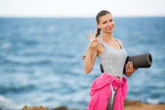 Woman with Mat for fitness on the coast stock photo