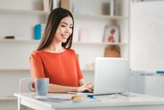 Woman on maternity leave having remote work. Remote work. Beautiful dark-haired woman on maternity leave feeling happy while having remote work royalty free stock photography