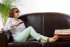 A woman of mature age  watch TV with  3D glasses Stock Photos