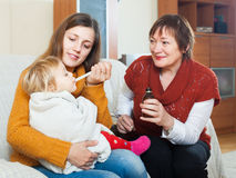 Woman with mature mother giving medicinal sirup to toddler. Young women with mature mother giving medicinal sirup to toddler at home Royalty Free Stock Photos