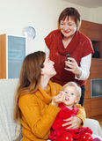 Woman with mature mother giving  sirup to sick toddler Royalty Free Stock Photo
