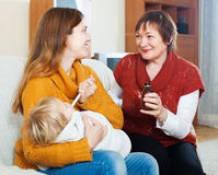 Woman with mature mother giving  syrup to unwell baby Stock Photos