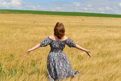 Woman in maxi dress standing on  rye field Royalty Free Stock Photo