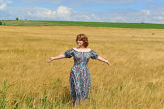 Woman in maxi dress standing on  rye field Stock Photography