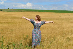 Woman in maxi dress standing on  rye field Royalty Free Stock Photos