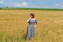 Woman in maxi dress standing on  rye field Royalty Free Stock Image