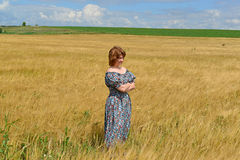 Woman in maxi dress standing on  rye field. Woman in maxi dress standing on the rye field Royalty Free Stock Images