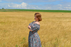 Woman in maxi dress standing on  rye field Stock Images