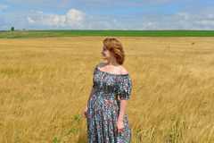 Woman in maxi dress standing on  rye field Royalty Free Stock Images