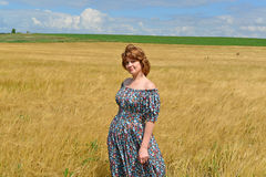 Woman in maxi dress standing on  rye field Stock Image