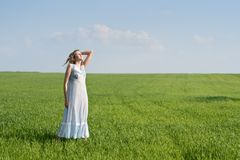 Woman in meadow. Young woman in nightdress on green meadow Royalty Free Stock Images