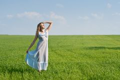 Woman in meadow. Young woman in nightdress on green meadow Royalty Free Stock Photography