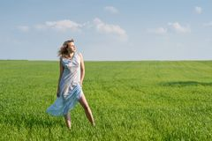 Woman in meadow. Young woman in nightdress on green meadow Stock Image
