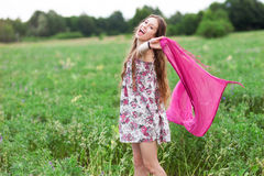 Woman in meadow holding scarf Stock Image
