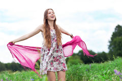 Woman in meadow holding scarf Royalty Free Stock Images