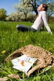 Woman meadow medicine. Young woman relaxing on a meadow with calendar and pills for allergic people in foreground royalty free stock photo