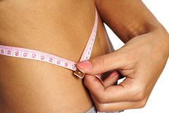 Woman measure her waist belly metre-stick. Woman measure her waist belly close-up by metre-stick close-up Stock Photos