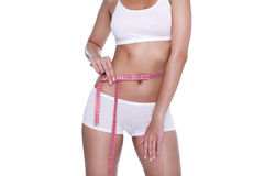 Woman and measure tape around her body. Slim woman and measure tape around her body on white background Stock Photography