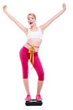 Woman with measure tape on scale celebrating weightloss. Fit fitness woman with measure tape happy blonde girl on weight scale celebrating weightloss progress Royalty Free Stock Images