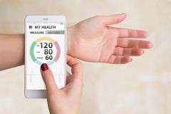 Woman measures blood pressure and pulse by mobile phone. With medical application stock images
