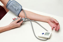 Woman measures her blood pressure Royalty Free Stock Photography