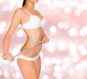 Woman measures her waistline. On an abstract background with blurred lights Stock Photo