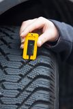 Woman measures tire tread of a car tire Royalty Free Stock Photo