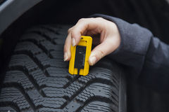 Woman measures tire tread of a car tire. A young woman is measuring the tread depth of her car tire. the proper depth in the tread of a tire can prevent royalty free stock image