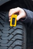 Woman measures tread of a car tire Stock Photo