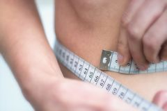 Woman measures very thin waist with measuring tape stock image