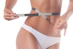 Woman measures waist circumference. on white. Fitness, weight loss and body care stock images