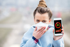 Woman measuring airpolution. Woman in protective mask holding smart phone with air polution measurement of PM10 outdoors Royalty Free Stock Photo