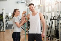 Woman measuring athletics man biceps. stock photos