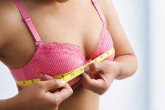 Woman measuring breast size. With yellow measuring tape on room Royalty Free Stock Photography