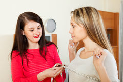 Woman measuring  bust of girlfriend. With measuring tape at home. Focus on blonde Stock Photography