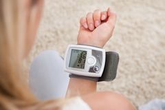 Woman measuring her blood pressure Stock Image