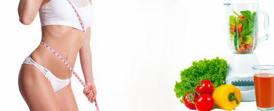 Woman measuring her body with a measure tape. Diet concept, fresh vegetables. Diet concept, fresh vegetables and fruits. Woman measuring her body with a measure Stock Image