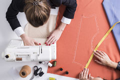 Woman measuring while her colleagues is sewing stock images
