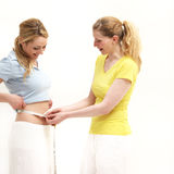 Woman measuring her friends waist Royalty Free Stock Image