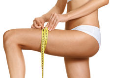 Woman is measuring her thigh with measuring tape Royalty Free Stock Photography