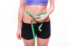Woman measuring her thin waist with a tape measure, close up Stock Photo