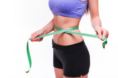 Woman measuring her thin waist with a tape measure, close up Royalty Free Stock Photo