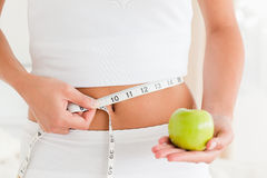 Woman measuring her waist while holding an apple Royalty Free Stock Images