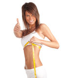 Woman measuring her waist, thumb up Royalty Free Stock Photo