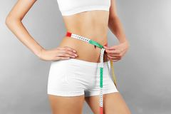 Woman measuring her waist. On color background Stock Photos