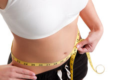 Diet Time. Woman measuring her waist with a yellow measuring tape, isolated in white Royalty Free Stock Images