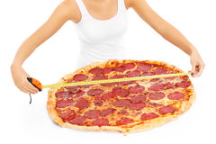Woman measuring huge pizza Stock Photography