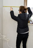 Woman measuring in new bathroom. Woman using a measuring tape in new room (bathroom), planning the placement of new furniture Royalty Free Stock Image