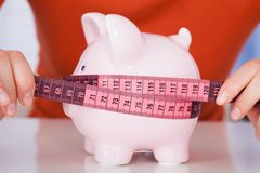 Woman Measuring Piggybank With Measure Tape Royalty Free Stock Photography