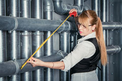 Woman measuring pipes distance Royalty Free Stock Photography
